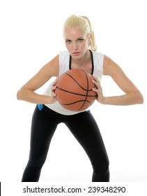 Sexy blonde female basketball player (model) posing for shot with ball in studio