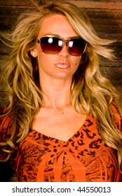 sexy blonde female fashion model wearing sunglasses against barn wood background