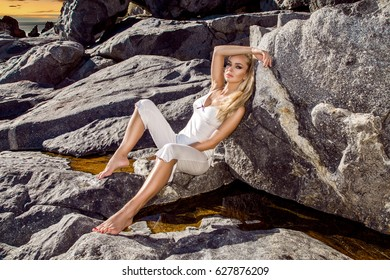 Sexy blonde female model sitting on rocks in sexy outfit