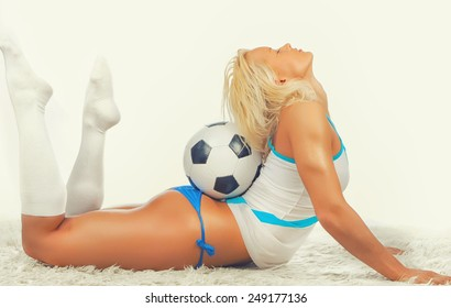 Sexy blonde female posing with a ball