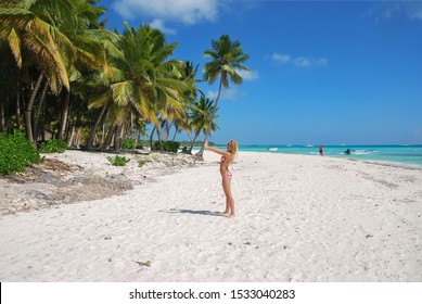Sexy blonde girl in bikini stands with her back turned on a white sandy beach on a background of palm trees.  Summer weed day. Blue sky.