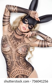 Sexy blonde girl with black mask with bunny ears isolated on white background. Lingerie model. Easter and Halloween sexy bunny concept. Lingerie like a tattoo.