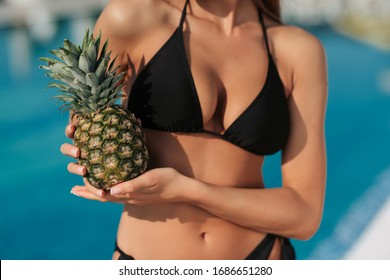 Sexy blonde girl in black swimsuit posing near swimming pool and holding pineapple. Beautiful young model posing and relaxing in hotel. Stunning woman