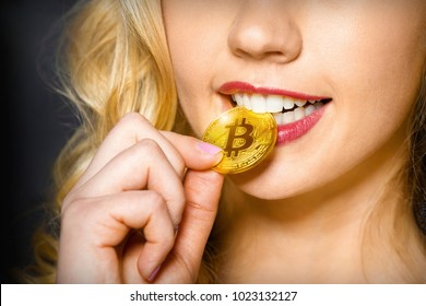Sexy blonde girl checks bitcoin for authenticity with the help her teeth. Bitcoin