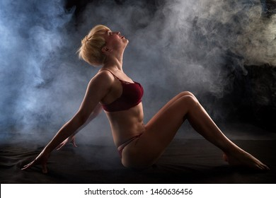 Sexy blonde girl during professional photo shoot in dark room with white smoke. Model in a red swimsuit. Black background