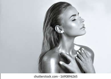 Sexy blonde girl with flawless skin and metallic glow on her neck and shoulders. Empty space. Monochrome toning