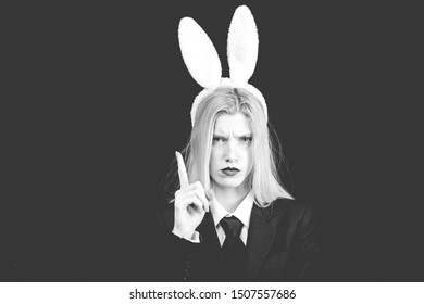 Sexy blonde girl with lace bunny ears. Sexy model dressed in costume Easter bunny. Beautiful young woman with bunny ears and blank poster on black background isolated