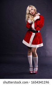 Sexy blonde girl with long curly hair, red lips, in a traditional Santa costume, white stockings, red shoes poses for the camera on a dark background.