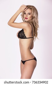 Sexy blonde girl posing in black lingerie over white background. Lace underwear set.