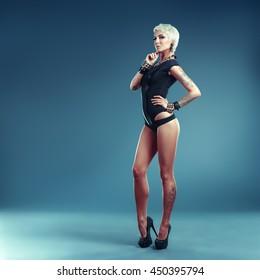 Sexy blonde girl with tattoos posing underwear