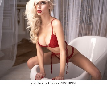 Sexy blonde girl in total red lingerie posing in modern bath looks so sexy and so excited with her red lips