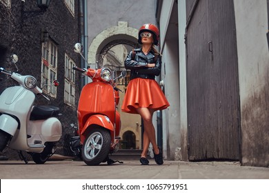 Sexy blonde girl wearing stylish clothes in sunglasses and helmet, standing with crossed arms on an old narrow street with two retro scooters.