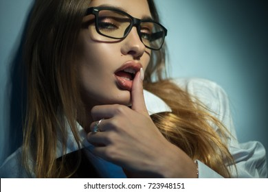 sexy blonde in glasses licks her finger and looks at the camera