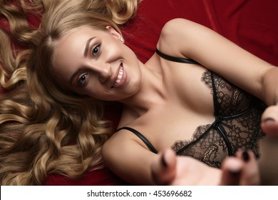 Sexy blonde in lingerie stretching hands to camera