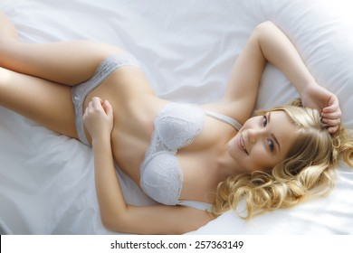 Sexy blonde lying on the white bed studio light background