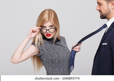 Sexy blonde manipulator woman pulling man by tie, holding eyeglasses