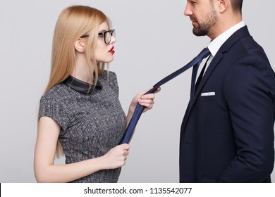 Sexy blonde manipulator woman pulling man by tie