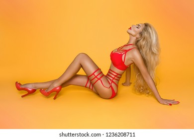 Sexy blonde model in red lingerie on a yellow background.