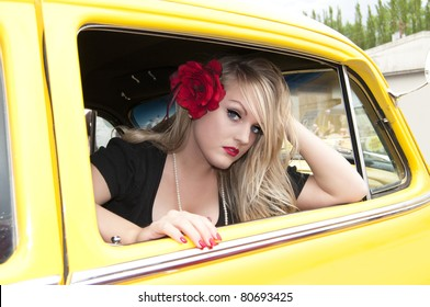 Sexy blonde pin up girl sitting inside classic car
