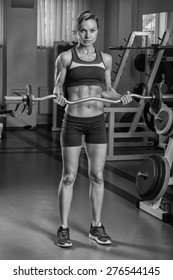 Sexy blonde trains his muscular body in the gym. Sport blonde. Strong girl.