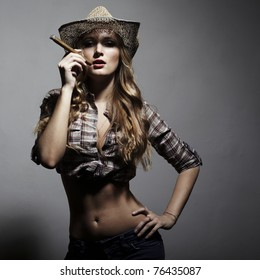 The sexy blonde woman with amazing hair in a hat and with a cigar in an image of the American cowboy