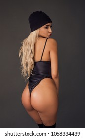 Sexy blonde woman back portrait wearing leather leotard and cap