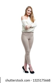 Sexy blonde woman in beige pants and white sweater, isolated on white background