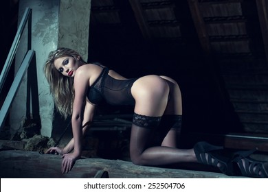 Sexy blonde woman in black underwear kneeling on timber at night, sensuality