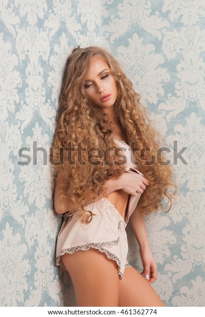 Sexy blonde woman with fashion make-up and curly hair in vintage bedroom. Skin and hair care concept