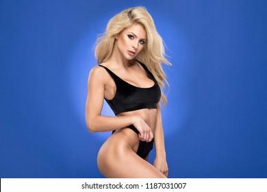 Sexy blonde woman inblack swimwear over blue background
