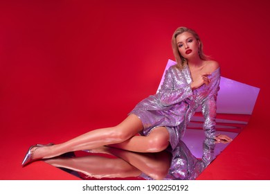 Sexy blonde woman with make-up, red lips and straight middle length wet hair in silver shining sequins dress sitting and posing on flexible mirror and red background. Fashion portrait