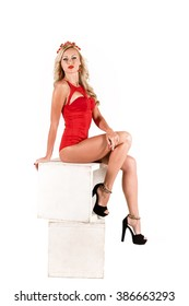 Sexy blonde woman posing in red dress over the white background