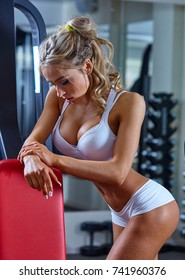 Sexy blonde woman is resting after exersise close to lifting machine at the gym