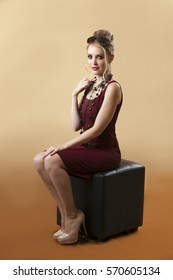 Sexy blonde woman in retro sixties outfit seated on black chair in front of soft gold background