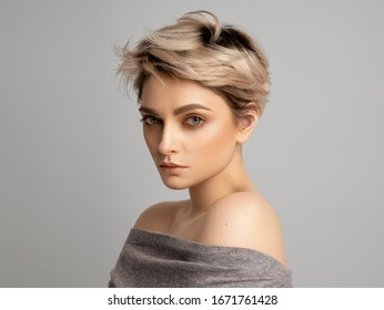 Sexy blonde woman with short hair posing in studio over gray background