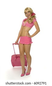 Sexy blonde woman in tiny pink outfit holding pink suitcase on white background.