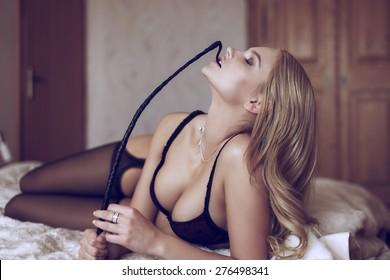 Sexy blonde woman in underwear bite whip, bdsm