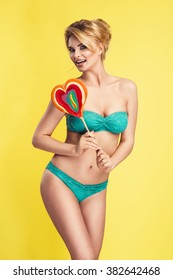 Sexy blonde woman wearing green bikini, holding big lollipop posing on bright yellow background. Perfect body. Skin care and cosmetics