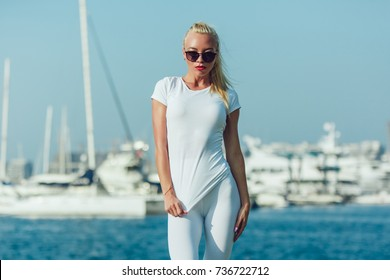 Sexy blonde woman in a white T-shirt is standing in the port. Mock-up.
