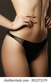 Sexy body of a beautiful woman. Beautiful woman body. Perfect shining skin for summer. Slim tanned woman's body. Isolated over black background. Beautiful sexy female slim tanned body