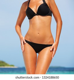 Sexy body on blue sea and sky background. Woman in black bikini on the summer beach. Diet and fitness concept. Beautiful tanned summer woman body