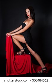 sexy body and sexy poses wearing black dress on black background and red fabric