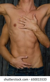 Sexy body. Two beautiful guys without a shirt are hugging. Sex and passion. Love and tenderness.