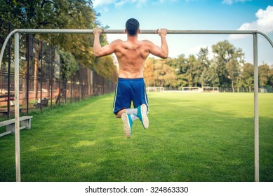 sexy bodybuilder working out in park, doing chin ups and push ups. Male fitness player training outdoors