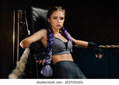 Sexy boxing girl stands leaned on ropes of competition ring. Fashionable portrait of luxurious female model. Beautiful braiding kanekalon pigtails hairstyle, wearing top, leggings and gloves.
