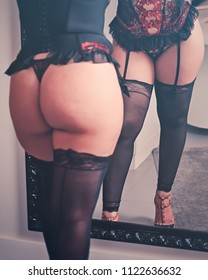 sexy brazilian girl in front mirror with big breasts and butt in black lingerie with red