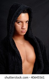 Sexy brazilian young man with black bathrobe over black background.