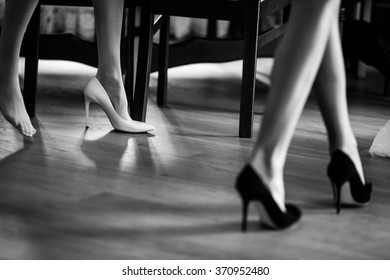 Sexy bride and bridesmaids in elegant white and black shoes walking on floor b&w closeup