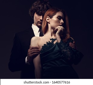 Sexy bright foxy hairstyle female woman in fashion green dress posing with handsome man in black suit clothing on dark shadow studio background. Closeup portrait. Toned color. Art