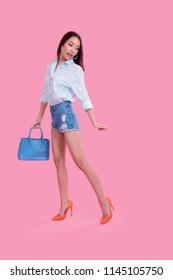 c4a4ef29f4 Sexy brunette Asian girl in floral white shirt ripped denim shorts with  pastel blue handbag and